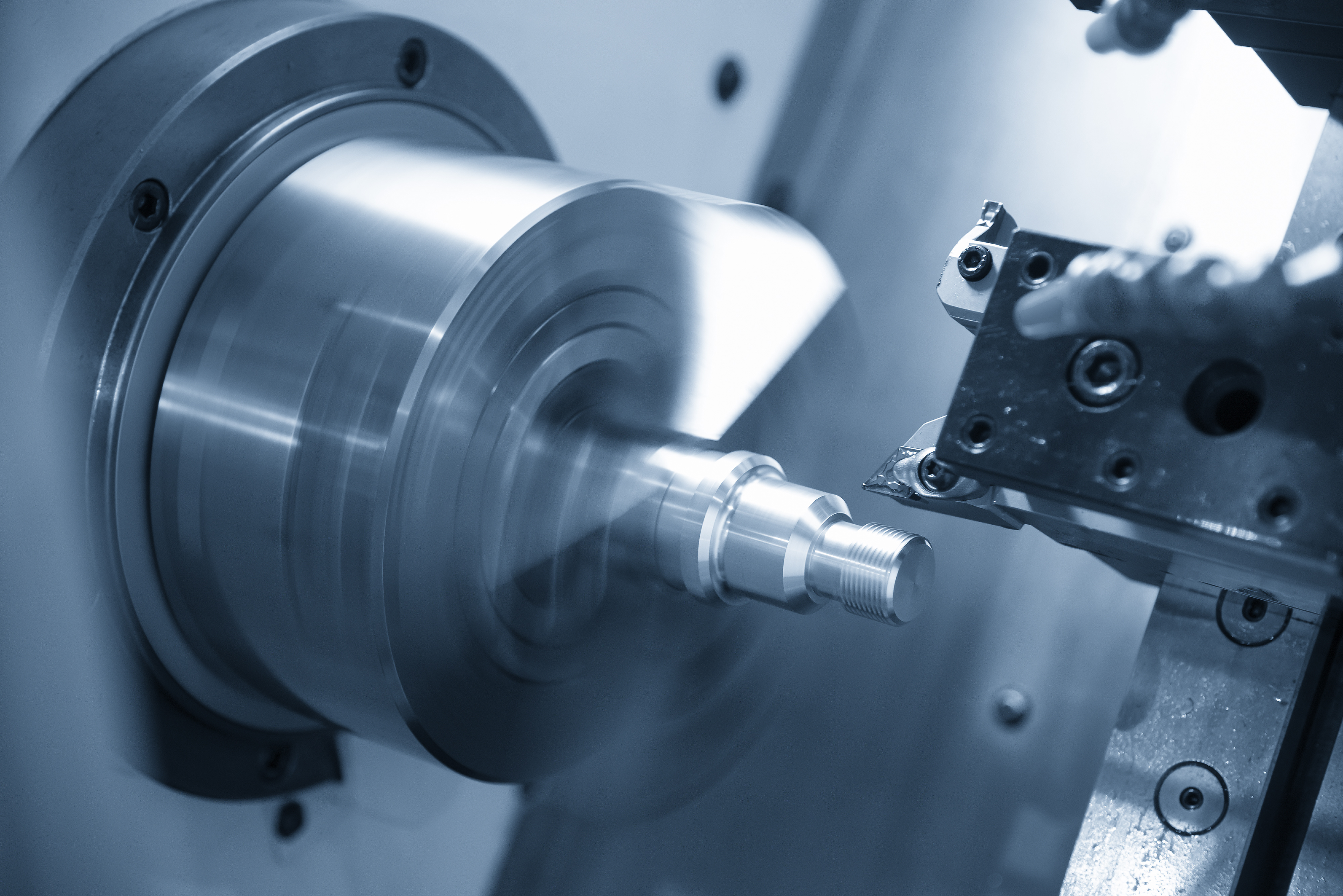 The  CNC lathe machine or turning machine  cutting the thread at the steel shaft.The threading process on the CNC lathe machine .